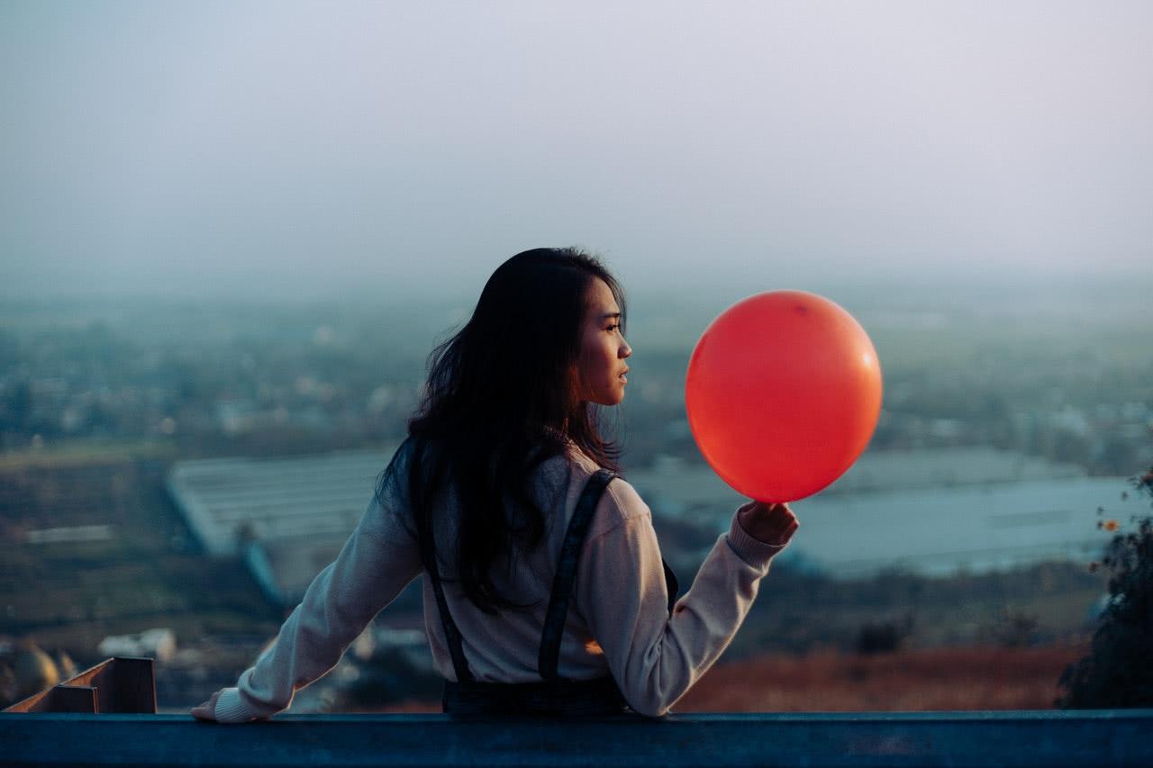 woman-wearing-white-dress-shirt-while-holding-red-balloon-3526416.jpg